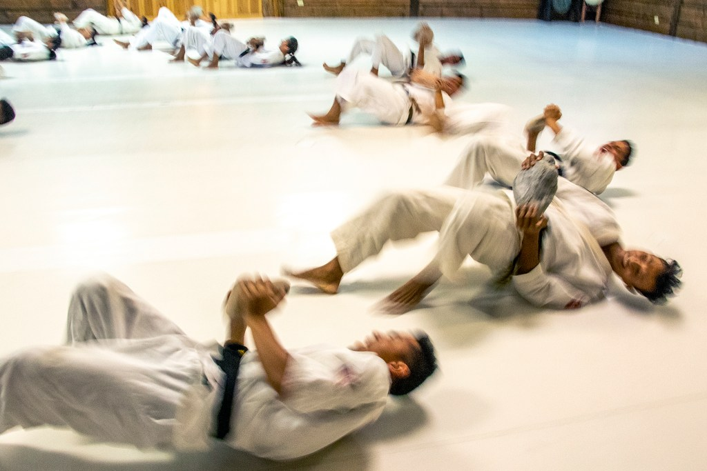 Nepali Soldiers exercise, crawling backwards while holding large stones, at Aikido Nippon Kan, Aug. 15, 2019. (Kevin J. Beaty/Denverite)