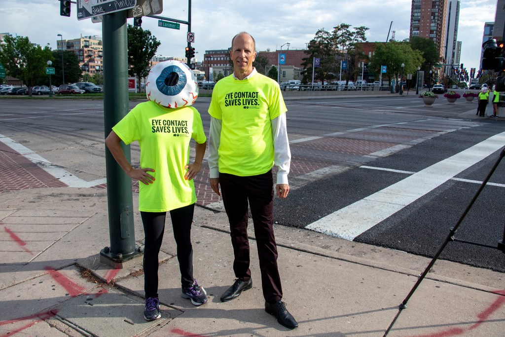 Sam Cole, safety communications manager with CDOT, poses with an eyeball promoting eye contact awareness along Speer Boulevard, Sept. 4, 2019. (Kevin J. Beaty/Denverite)