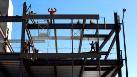 Construction workers above Brighton Boulevard work it for the camera, Five Points, Sept. 24, 2019. (Kevin J. Beaty/Denverite)