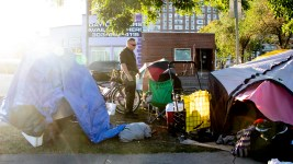 A Denver Police officer distributes notices telling residents living in encampments near Sonny Lawson Park that they must leave. Sept. 26, 2019. (Kevin J. Beaty/Denverite)