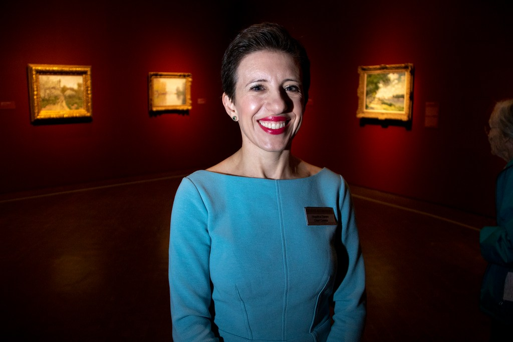 "Angelica Daneo, chief curator and curator of European art before 1900 for the Denver Art Museum, poses for a portrit inside ""Claude Monet: The Truth of Nature."" Oct. 17, 2019. (Kevin J. Beaty/Denverite)"