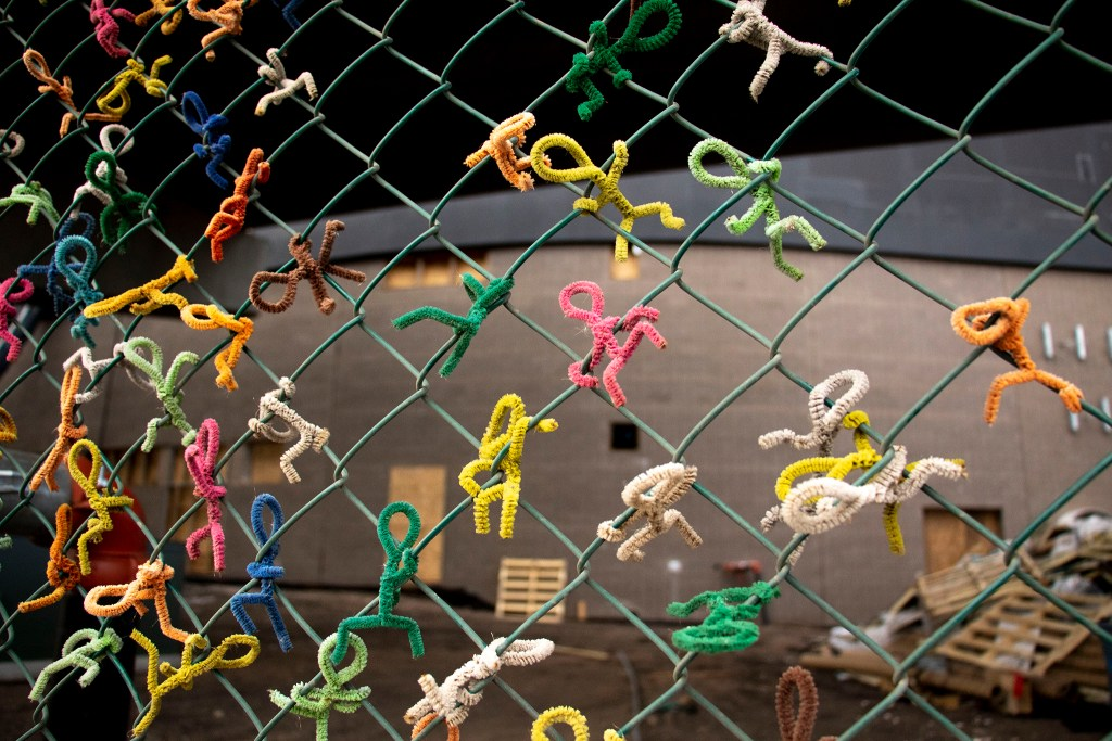 Little pipe cleaner figures cling to the fence surrounding Meow Wolf's future Sun Valley location, Oct. 26, 2019. (Kevin J. Beaty/Denverite)