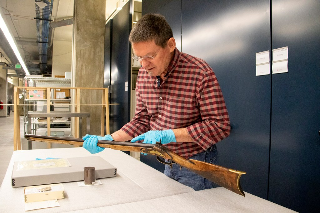 "History Colorado curator James Peterson shows a reporter ""Noisy"" Tom Pollack's deadly long rifle inside the museum's archive space downtown, Oct. 15, 2019. (Kevin J. Beaty/Denverite)"