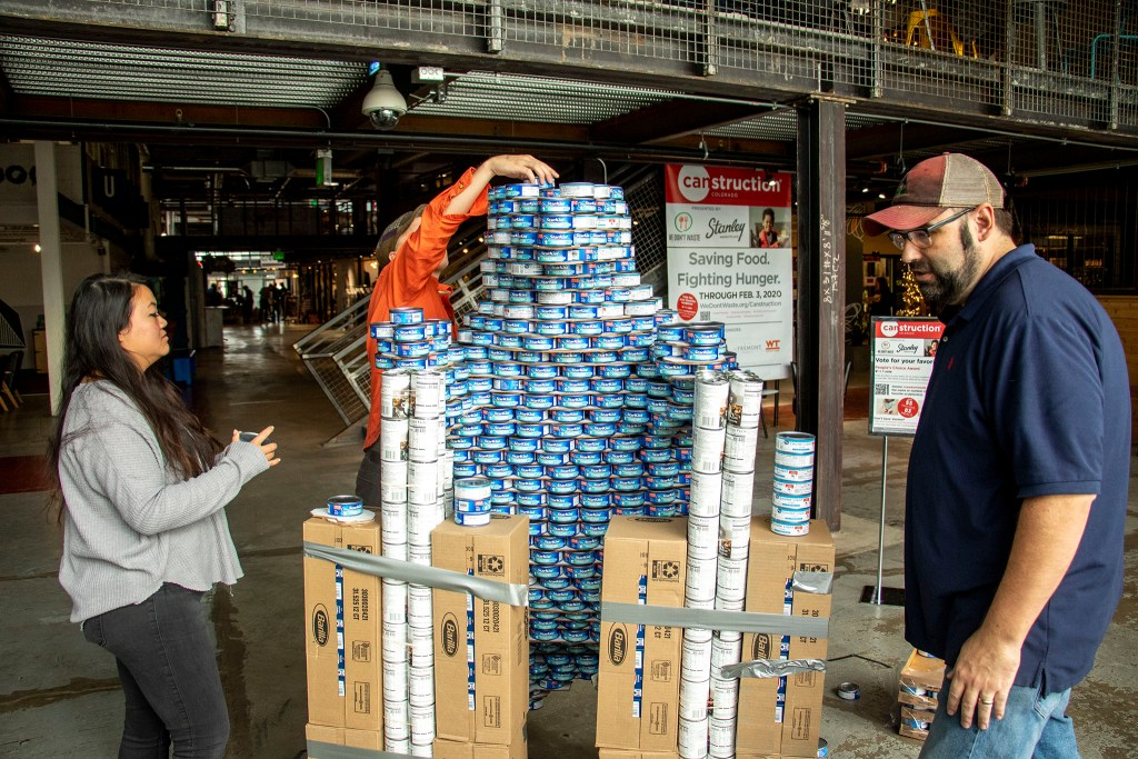 "Aileen Tang (left to right), Luke Buranen and Brian Young build a big blue bear during We Don't Waste's ""Can-struction"" show at Stanley Marketplace. Nov. 15, 2019. (Kevin J. Beaty/Denverite)"