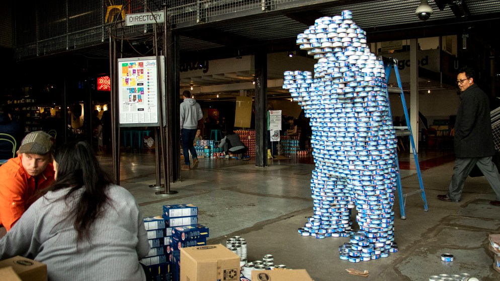 "Aileen Tang and Luke Buranen build a big blue bear during We Don't Waste's ""Can-struction"" show at Stanley Marketplace. Nov. 15, 2019. (Kevin J. Beaty/Denverite)"
