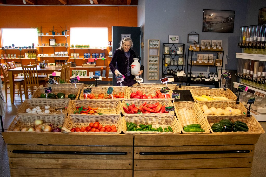 Di Collingwood sprays water on vegetables on sale at The Co-Op at 1st in Barnum West, Nov. 20, 2019. (Kevin J. Beaty/Denverite)