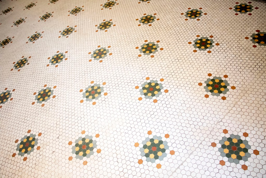 A historic tile floor inside the Quayle apartments on Broadway, Nov. 21, 2019. (Kevin J. Beaty/Denverite)