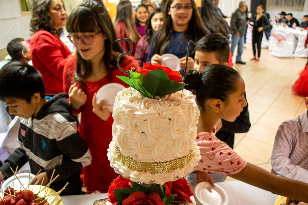 Kids dig into candy and chocolate before Kim Ramos' fancy quinceañera cake was cut. Ministerio Hispano Presbyterian Church, Dec 14, 2019. (Kevin J. Beaty/Denverite)