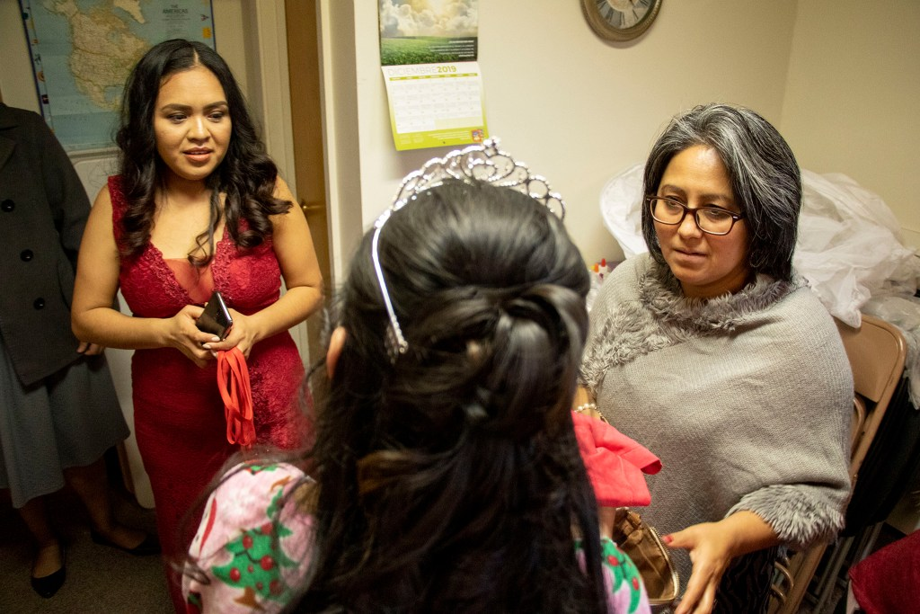 Kim Ramos' mother, Erika Piedra Avendaño (left), and a member of her church, Delfina Solano, inspect Ramos' makeup before her quinceañera ceremony at Ministerio Hispano Presbyterian Church, Dec 14, 2019. (Kevin J. Beaty/Denverite)