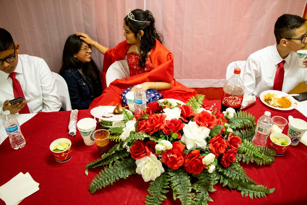 Kim Ramos jokes with Sandra Escobedo, her friend and classmate, as David Argueta and Jared Pallares text memes to each other across the table. Ramos' quinceañera at Ministerio Hispano Presbyterian Church, Dec 14, 2019. (Kevin J. Beaty/Denverite)