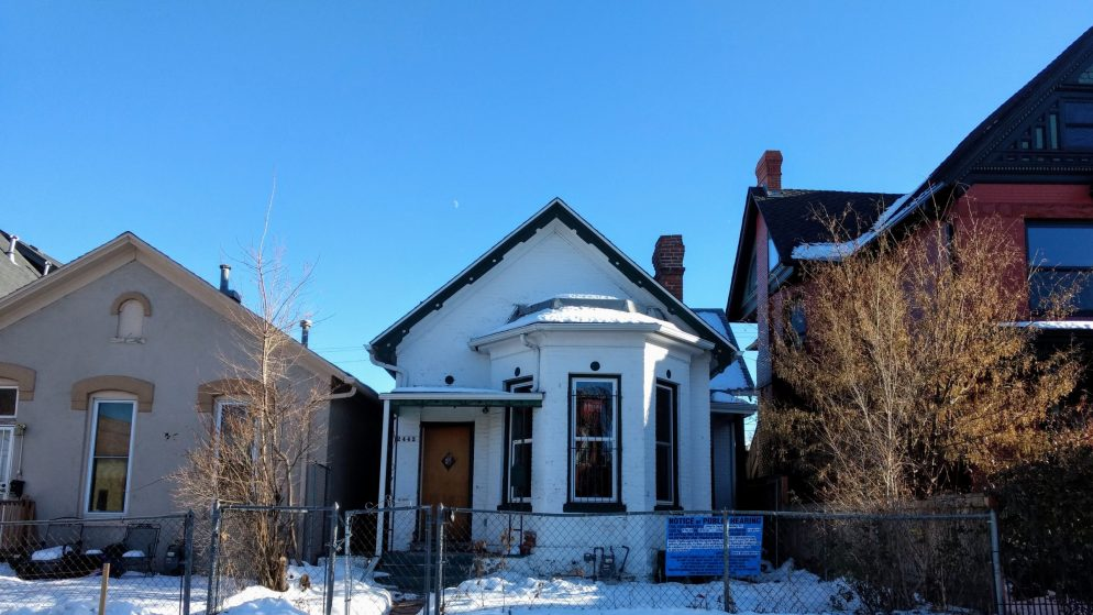 A Victorian bungalow, pictured on Dec. 3, 2019, sits in front of a new house under construction at 2444 Tremont Place. (Donna Bryson/Denverite)