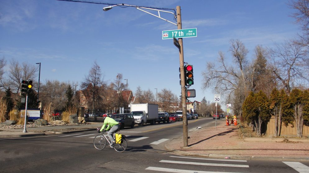 A cyclist rides at the intersection of Quebec Street and 17th Avenue on Monday, Dec. 16, in Denver. (Esteban L. Hernandez/Denverite)