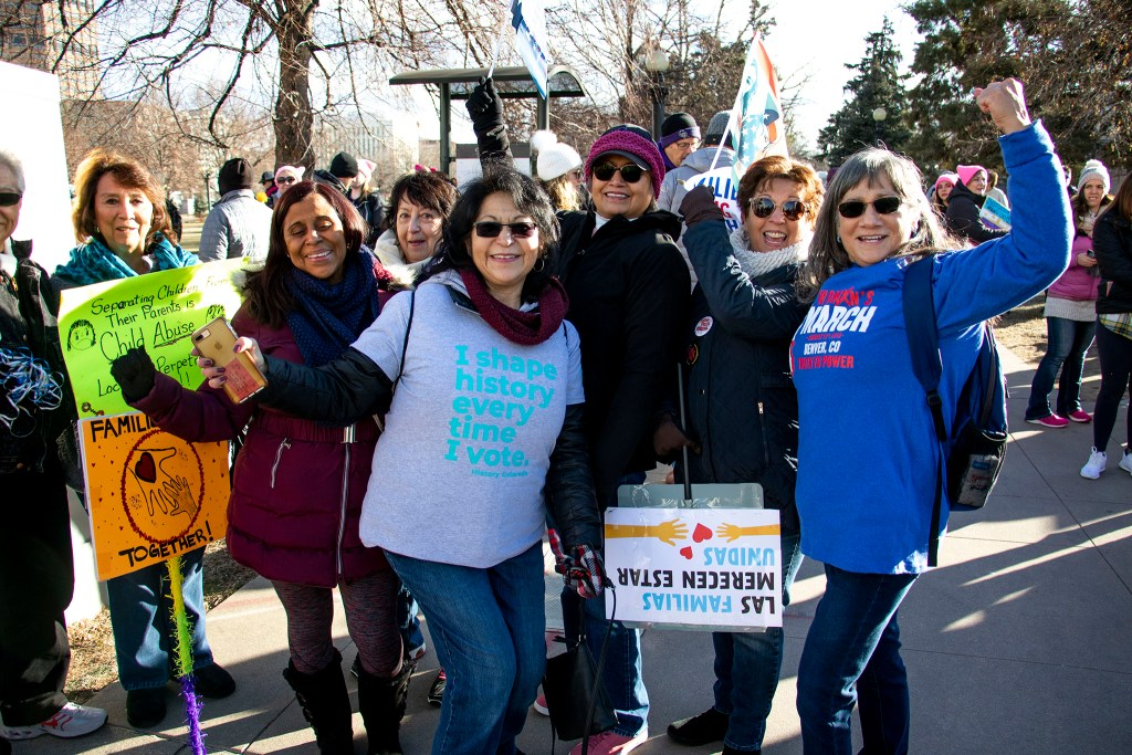 Ernestine Garcia (right) poses with a photo with friends and family before the Denver Womxn's March began. Jan. 18, 2020. (Kevin J. Beaty/Denverite)