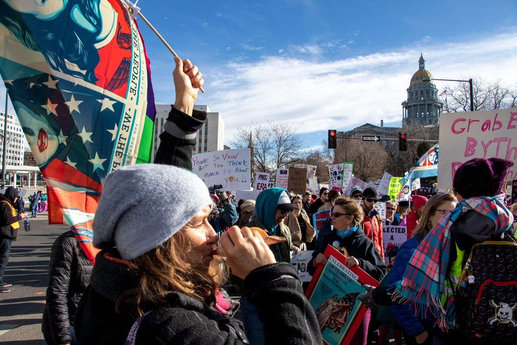 Kelly Bartell blows on a shell horn on Colfax Avenue during the Denver Womxn's March, Jan. 18, 2020. (Kevin J. Beaty/Denverite)