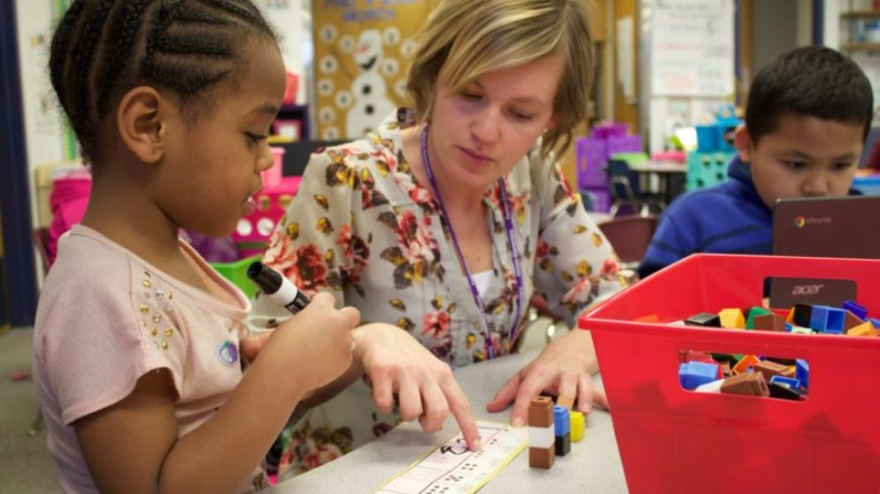 A kindergarten teacher at Kenton Elementary in Aurora, Colorado helps a student practice saying and writing numbers. (Yesenia Robles/Chalkbeat)