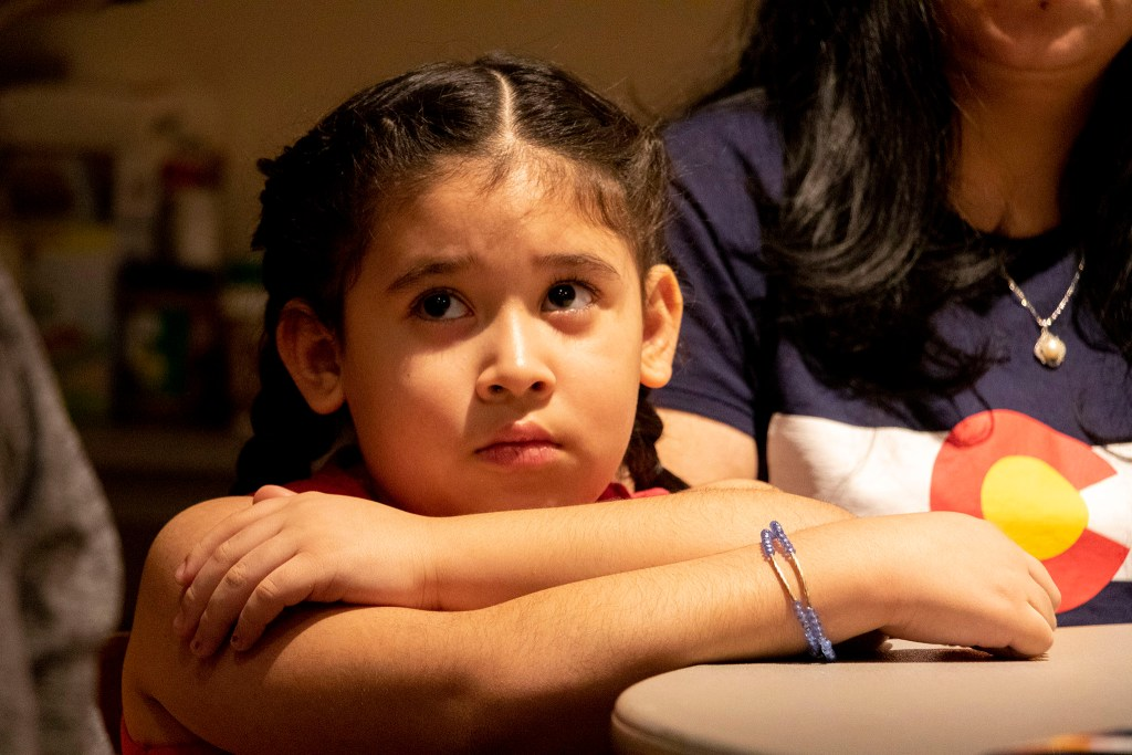 Jorge Ávila's daughter, Sherlyn, sits at a table in the basement of Park Hill United Methodist Church and Temple Micah while he speaks to a reporter, Feb. 11, 2020. (Kevin J. Beaty/Denverite)