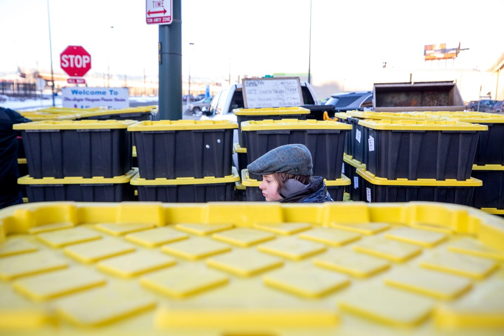 A kid stands between crates of groceries bound for area schools, prepared by Food For Thought Denver, on a very cold morning beneath the Colfax viaduct, Feb. 21, 2020. (Kevin J. Beaty/Denverite)