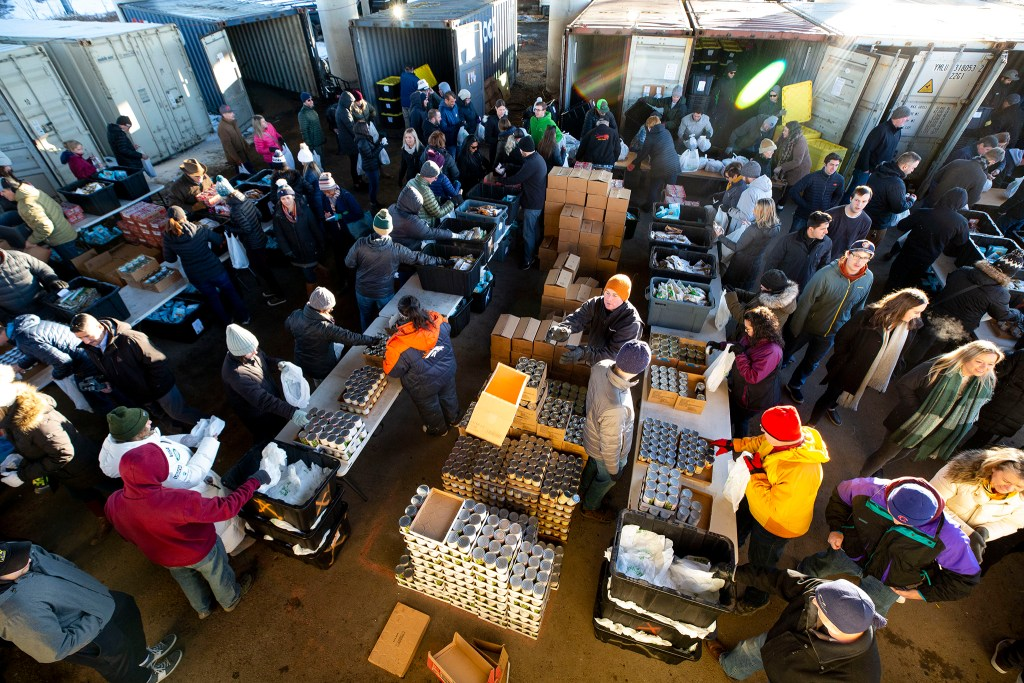 Volunteers with Food For Thought Denver pack bags of groceries beneath the Colfax viaduct, Feb. 21, 2020. (Kevin J. Beaty/Denverite)