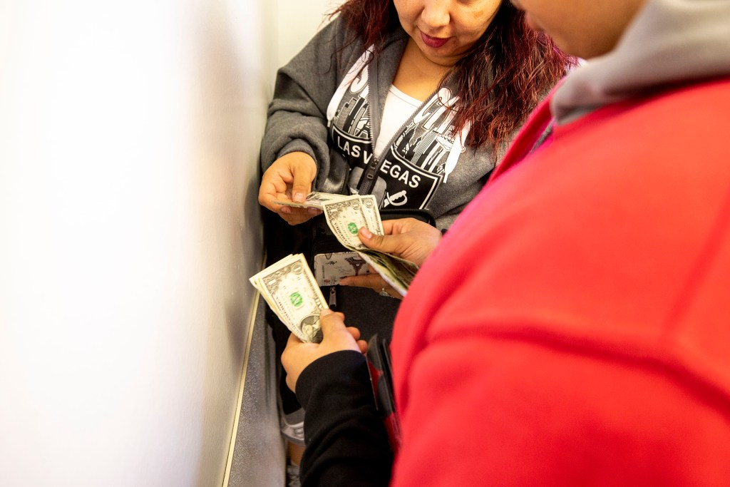 Christina Zaldivar gives her son, Diego, some money as she drops him off at Sunday school. March 7, 2020. (Kevin J. Beaty/Denverite)