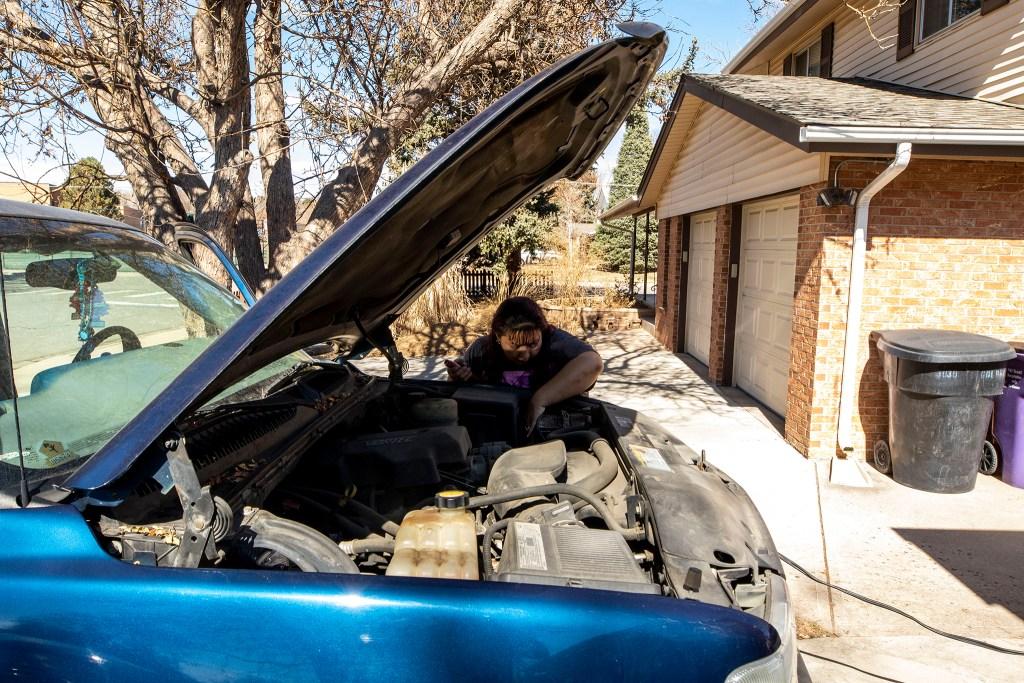Christina Zaldivar works on a dead car battery in her driveway. March 7, 2020. (Kevin J. Beaty/Denverite)