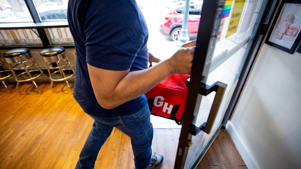 Julian Rai gingerly opens the door after grabbing a Grubhub order at Ice Cream Riot in Capitol Hill. March 13, 2020. (Kevin J. Beaty/Denverite)