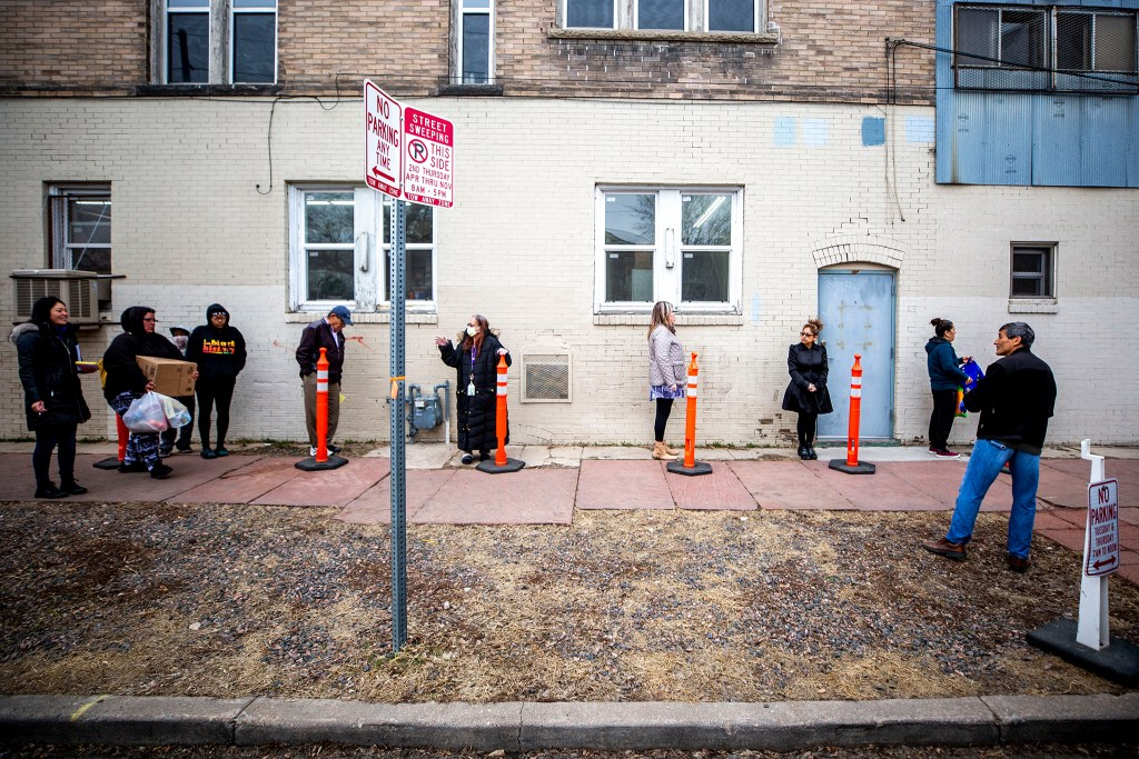 People line up for their monthly allotment of groceries from the Twin Parishes food pantry in Cole. It's the first time in 40 years they've had to do this outside. March 17, 2020. (Kevin J. Beaty/Denverite)