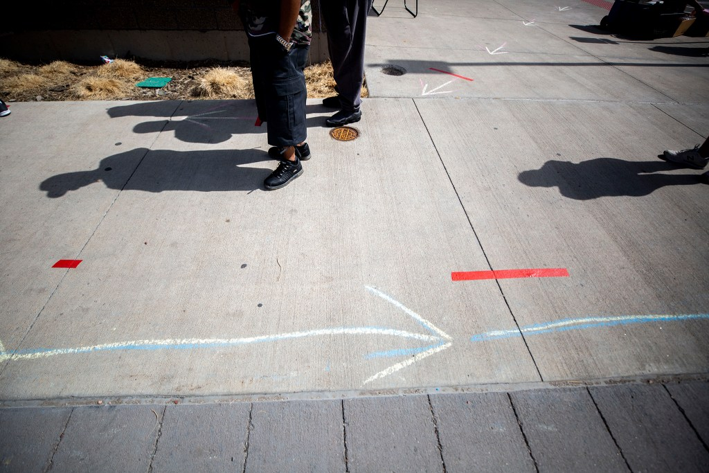 Visitors to Metro Caring food pantry had to stand at marked intervals for social distancing outside due to COVID-19 concerns, March 18, 2020. (Kevin J. Beaty/Denverite)