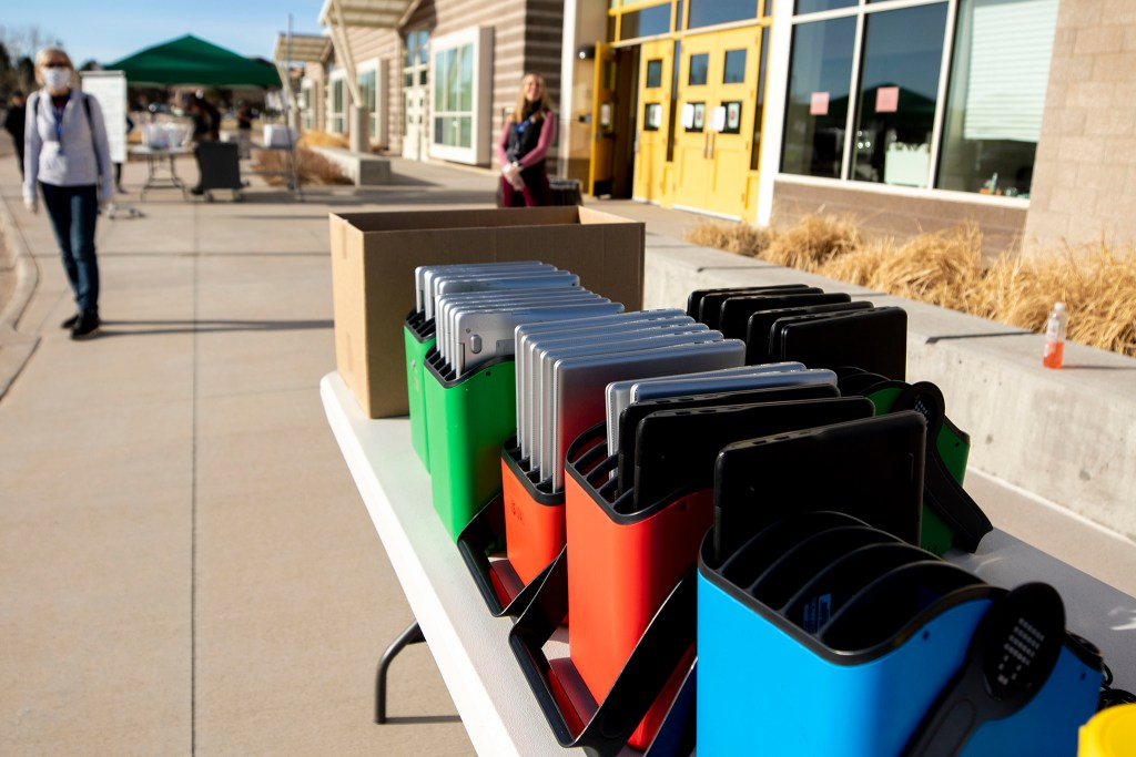 """Joe Shoemaker School staff distribute laptops to families with kids who need to study at home while COVID-19 """"social distancing"""" orders are in place. March 25, 2020. (Kevin J. Beaty/Denverite)"""