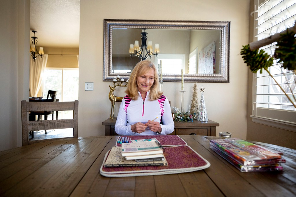 "Debbie Fox sits at the dining room table in her Arvada home where she's been making art during mandated ""social distancing."" March 26, 2020. (Kevin J. Beaty/Denverite)"