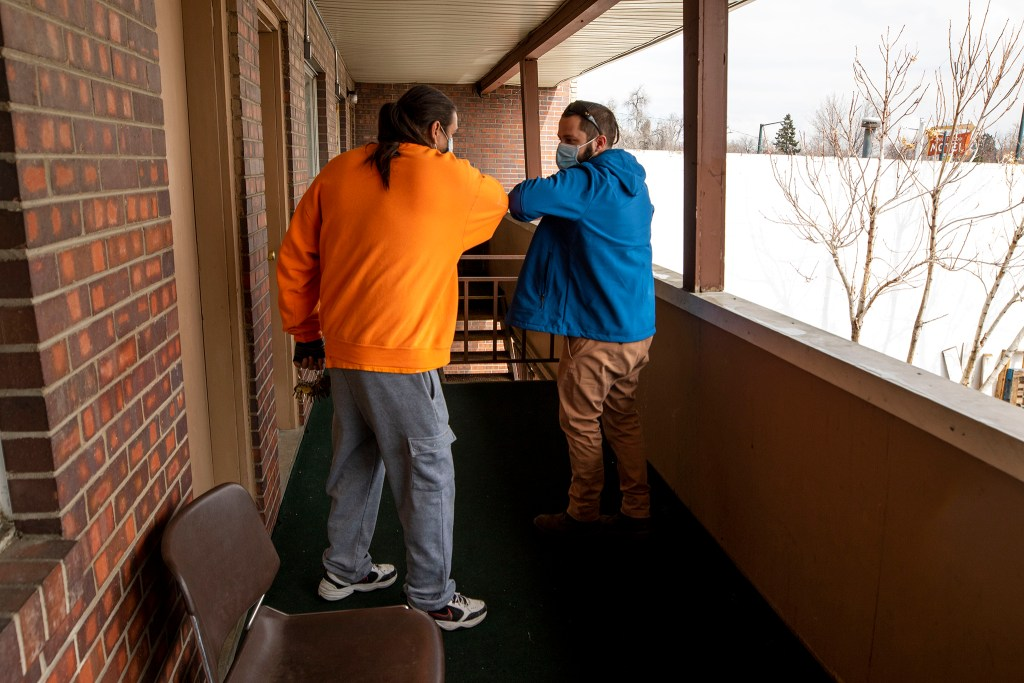 Driftwood Motel manager Chuck Perkins bumps elbows with Mental Health Center of Denver case manager Evan Robertson. April 3, 2020. (Kevin J. Beaty/Denverite)