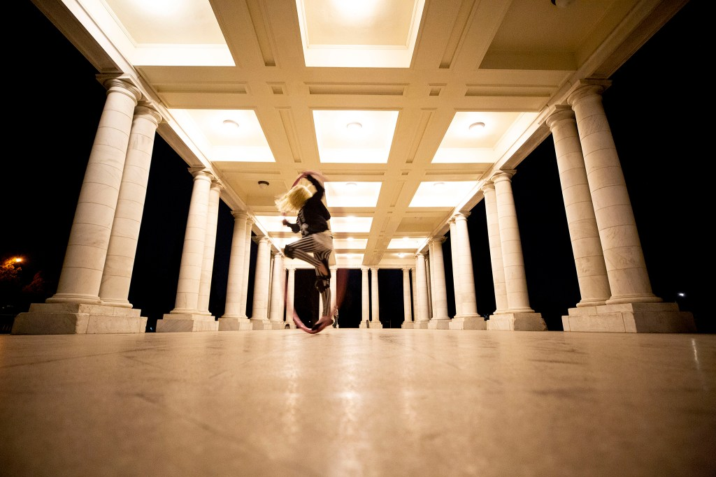 Becca Doyle spins inside a giant hoop in the Cheesman Park colonnade. April 7, 2020. (Kevin J. Beaty/Denverite)