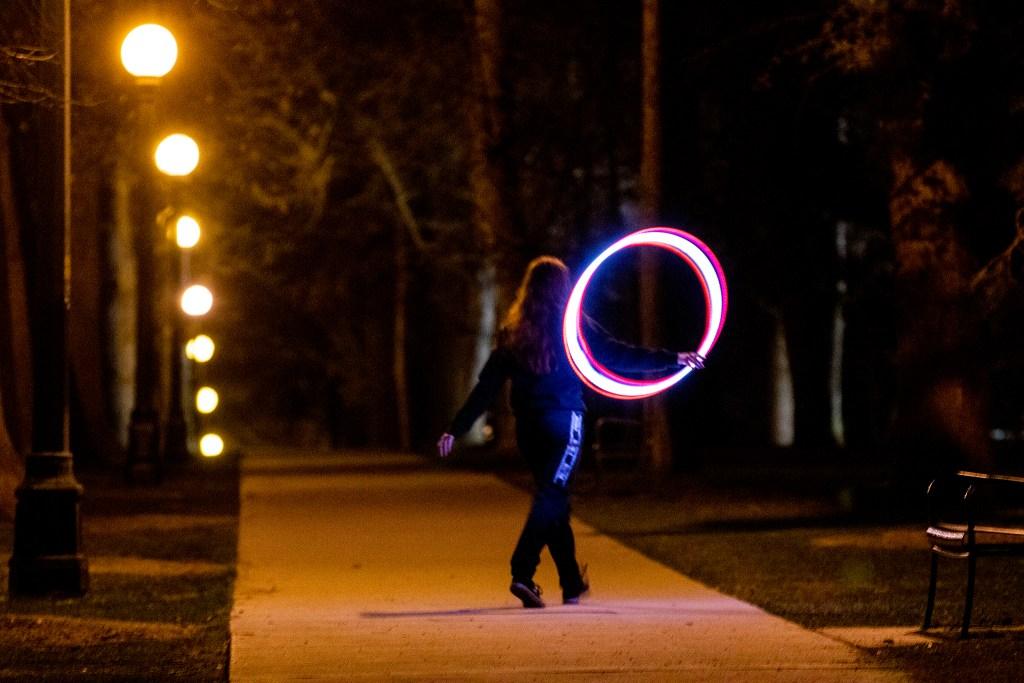 A woman walks through Cheesman Park with a glowing hula hoop. April 7, 2020. (Kevin J. Beaty/Denverite)