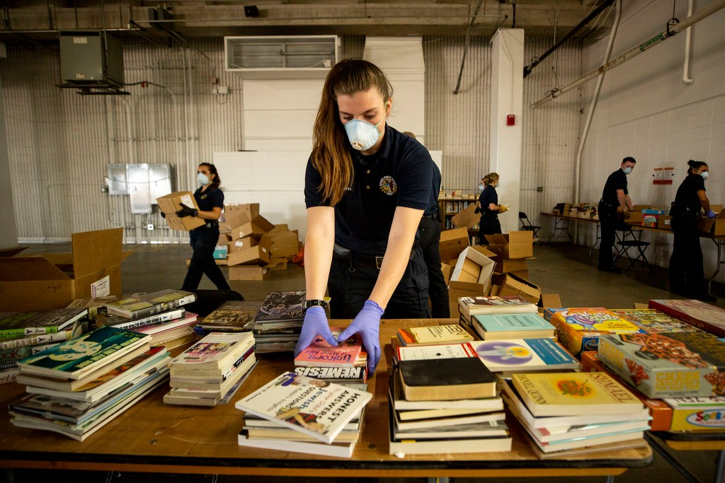 Vasi Reiva, a Denver Division of Public Safety cadet, helps set up a library inside the makeshift shelter for unhoused men at the National Western Center. April 8, 2020. (Kevin J. Beaty/Denverite)
