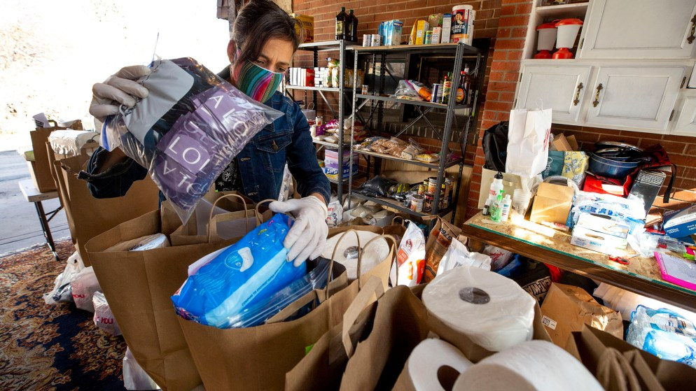 Michelle Lasnier, owner of Ruby's Pantry, packs bags of food and home goods inside her garage off South Pearl Street. April 21, 2020. (Kevin J. Beaty/Denverite)