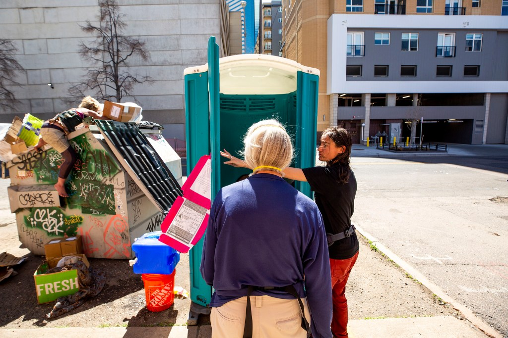 Terese Howard (right) and Dianne Thiel inspect a port-a-potty that their organization, Denver Homeless Out Loud, has paid to be installed and serviced on here on 21st Street. The cleaning log inside has been updated as people camping nearby have serviced it. April 28, 2020. (Kevin J. Beaty/Denverite)