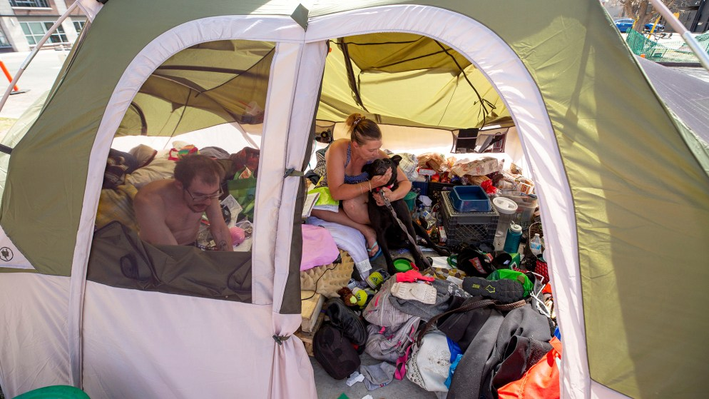 Richard and Misty Splud inside their tent on 21st Street with their dog, dirty kid. April 28, 2020. (Kevin J. Beaty/Denverite)