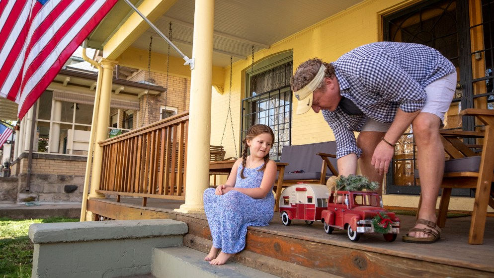 """Woody Faircloth and Luna, his daughter and """"sidekick,"""" play with a toy trailer on their front porch near City Park. April 29, 2020. (Kevin J. Beaty/Denverite)"""