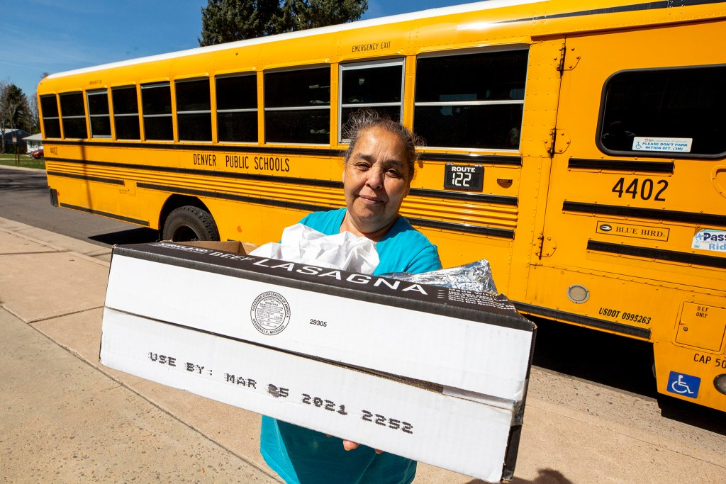 Rosario Iniguez holds bags of food she recieved from a DPS bus parked outside of Schmitt Elementary School in Ruby Hill. May 6, 2020. (Kevin J. Beaty/Denverite)