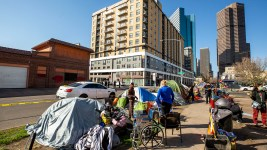 Denver police ensure people living on the street in Five Points pack up and move before the sidewalk is cleaned. May 7, 2020. (Kevin J. Beaty/Denverite)