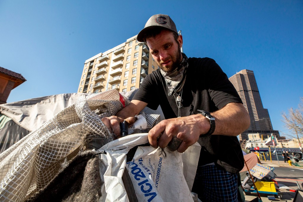 Dustin Fitzpatrick deconstructs his home on Curtis Street in Five Points at the orders of Denver Police. May 7, 2020. (Kevin J. Beaty/Denverite)