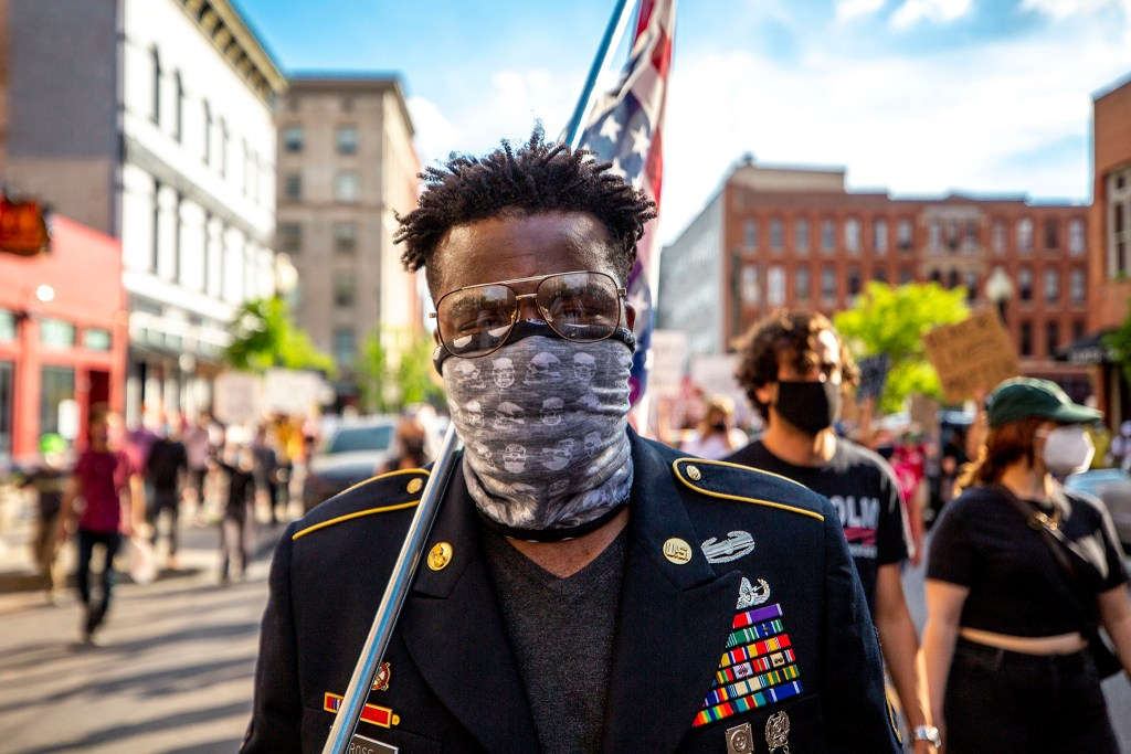 Aubrey Rose, an 18-year U.S. Army veteran, marches with an upside-down American flag over his shoulder. A march reacting to the death of George Floyd comes face to face with authorities at 20th Street and Chestnut Place. May 28, 2020. (Kevin J. Beaty/Denverite)