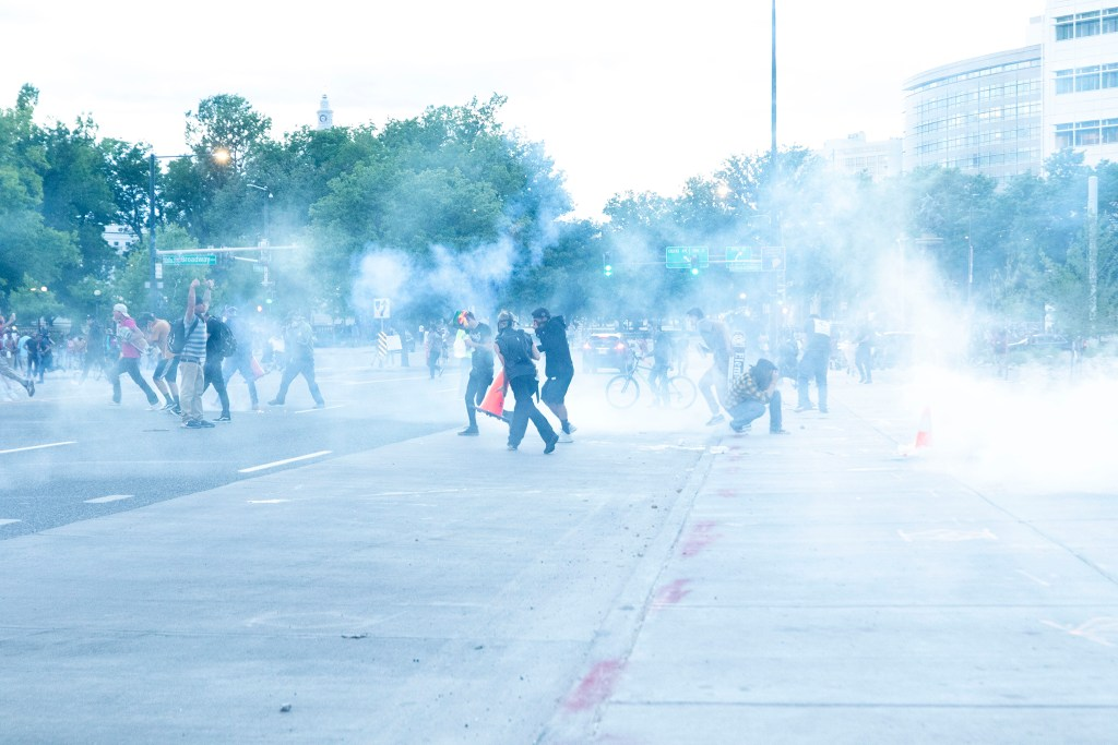 Protesters run as Denver Police officers deploy several cans of tear gas on Colfax Avenue. May 29, 2020. (Kevin J. Beaty/Denverite)