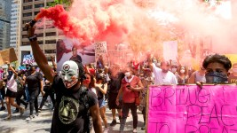 A man in a mask led a huge march with a smoke bomb on the third day of protests in reaction to the killing of George Floyd. May 30, 2020. (Kevin J. Beaty/Denverite)