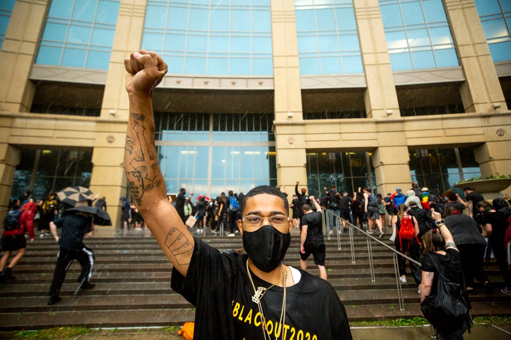 Racquise McClain, Elijah McClain's cousin, stays put as rain began to fall during a rally against police brutality in front of the Aurora Municipal Center. June 6, 2020. (Kevin J. Beaty/Denverite)