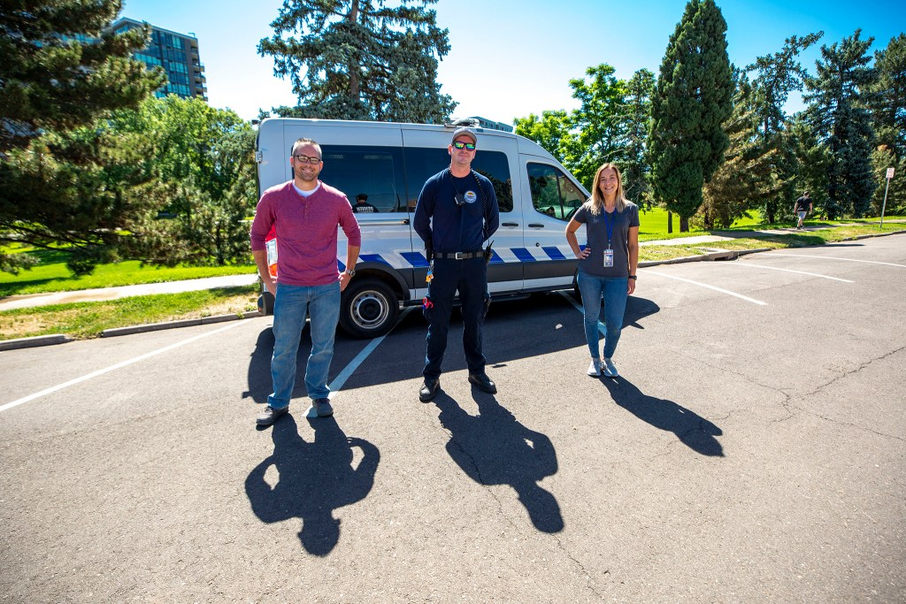 Chris Richardson and Carleigh Sailon with the Mental Health Center of Denver (left and right) and Spencer Lee, a Denver Health paramedic, stand in front of the Support Team Assisted Response's new van. June 8, 2020. (Kevin J. Beaty/Denverite)