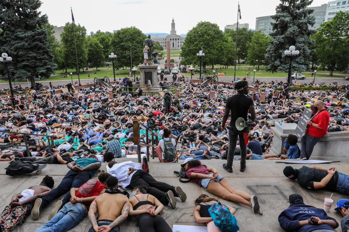 Activist Nate Smith, with a megaphone, looks on as protesters remember George Floyd by laying face down on the ground in front of the State Capitol on June 3, 2020. (Hart Van Denburg/CPR News)