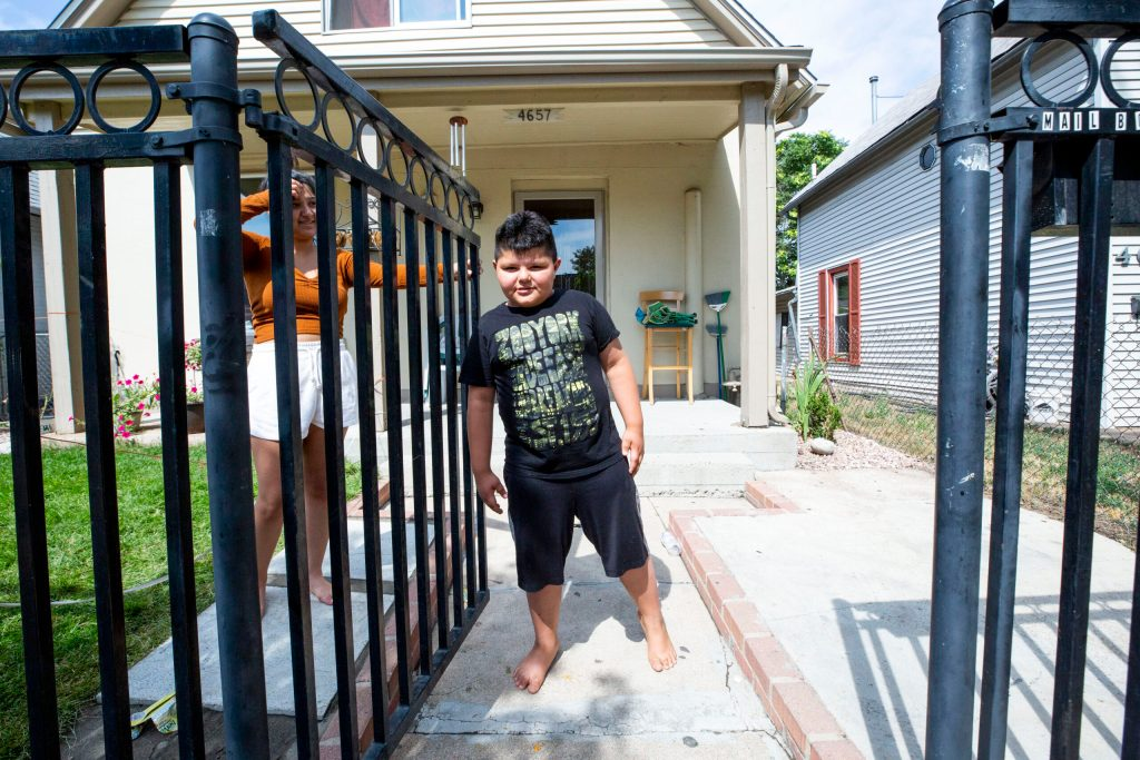 Christopher Guerrero stands in his front yard on Elyria Swansea's Columbine Street as his sister, Lydia, holds open the gate. July 22, 2020.