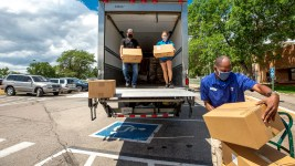 Enrique Moore, Robyn Hills and Marcus Thomas unload boxes from the USDA to the Southwest Family YMCA's food pantry. July 24, 2020.