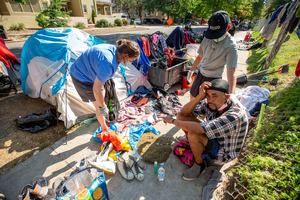 Frank McClure, a Morey Middle School student who's been distributing supplies at the tent encampment here all summer, comforts Christopher Johnson, whose wife left recently after they had a fight. Capitol Hill, Aug. 3, 2020.