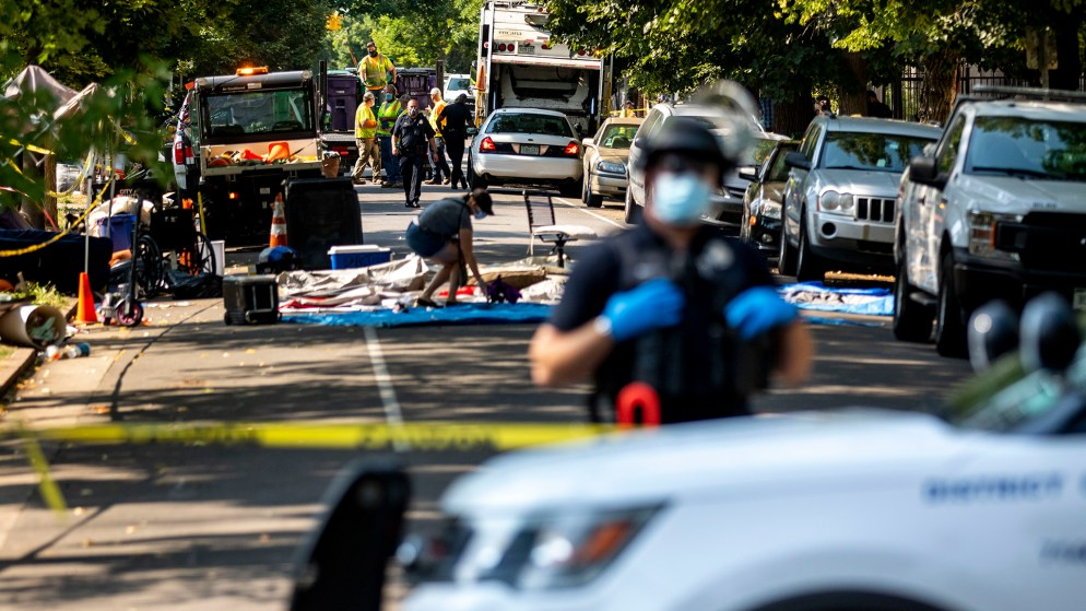 Denver Police officers enforce a cleanup of an encampment in front of Morey Middle School. Capitol Hill, Aug. 6, 2020.